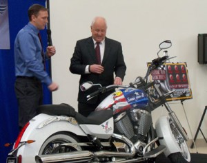 Ray Sorensen III (Left) and Iowa Lottery CEO Terry Rich unveil a motorcycle to be raffled-off.