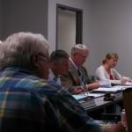 Iowa Western President Dr. Dan Kinney (Center, tan sport jacket) speaks at the meeting held in Atlantic.
