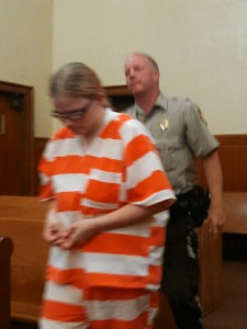 Leatha Kay Slauson enters the courtroom accompanied by Cass County Sheriff Darby McLaren. (Ric Hanson/photo)