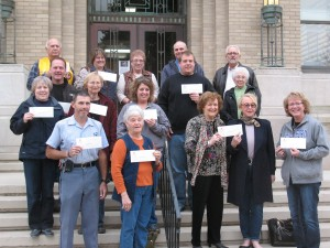 Representatives of the 14 non-profit organizations show-off their CCCF checks Friday on the steps of the Cass County Courthouse. (Ric Hanson/photo)
