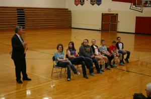 Pottawattamie County Sheriff Jeff Danker addresses the 7 students at an assembly Wednesday, who helped their classmates after a bus rollover accident. (Photo from Pott. Co. S/O Facebook page)