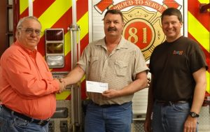 General Manager and President of Walnut Communications, Bruce Heyne presents a check to Fire Chief Paul Ward and Greg Heine on behalf of the Neola Fire Department.