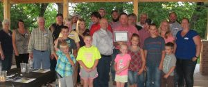 Allen Zellmer (Center, holding award) and his family and staff.